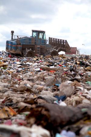 Truck flattening trash in landfill