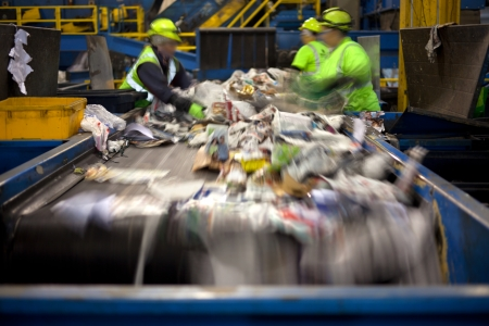 Workers separating paper and plastic on a conveyor belt in a recycling facility
