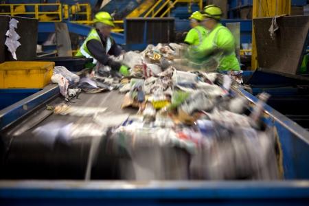 reciclaje de papel: Los trabajadores que separan el papel y el plástico en una cinta transportadora en una planta de reciclaje