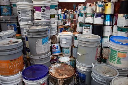 A load of old paint cans and glue buckets in a recycling facility 에디토리얼