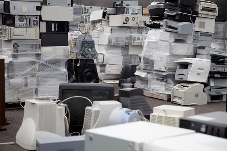 Piles de matériel électronique, imprimantes et ordinateurs dans un centre de recyclage