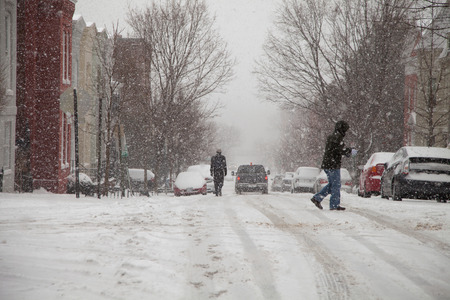 Pedestrians walking the streets of Georgetown in Washington DC under snow storm