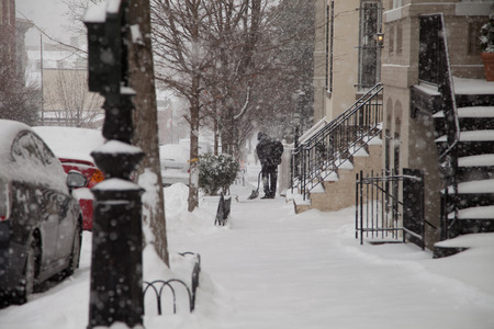 Man shoveling in front of its house during a snow storm in Washington DC Standard-Bild