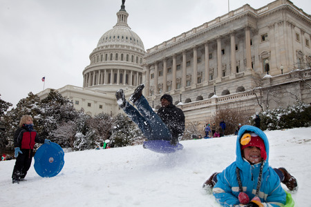 Unexpected snow day in Washington, DC  Schools were closed and children and adults are sledding on the US Capitol lawn  에디토리얼