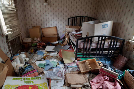Abandoned house s bedroom completely trashed with all kind of papers, boxes and clothes lying on the floor