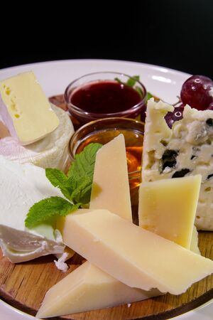 Cheeseboard. Parmesan, blue cheese, Camembert served with mint, honey, jam, grapes on a wooden board