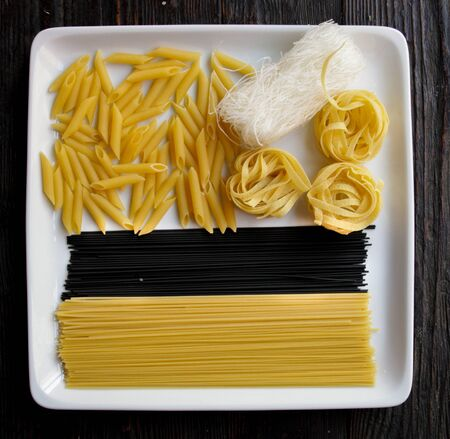 Close up of square white plate with various types of dry pasta.Dark wooden background Stockfoto