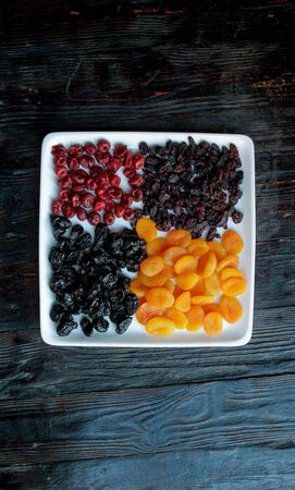 Dried fruits on a dark wooden background.Raisins, dried apricots, prunes, dried cherries on a square white plate.Copy space