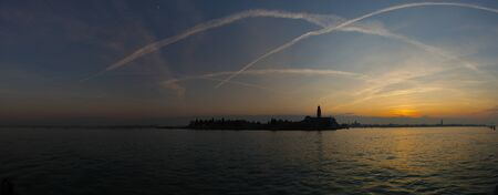 View of the San Michele island in Venice at sunset.Traces of airplanes in the sky. Stockfoto