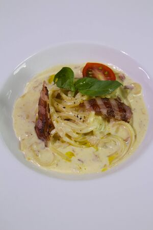 Spaghetti carbonara served with cheese, grilled bacon, cherry tomato, mint on a white plate.Close up.Copy spase.
