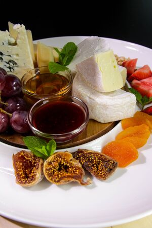 Cheese plate. Camembert cheese, Parmesan, blue cheese served with grapes, mint, jam, figs, honey, strawberries, dried apricots on a white plate. Stockfoto