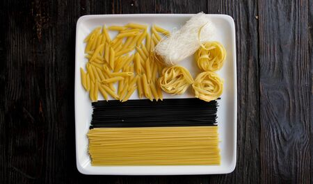 Close up of square white plate with various types of dry pasta.Dark wooden background.Copy space.