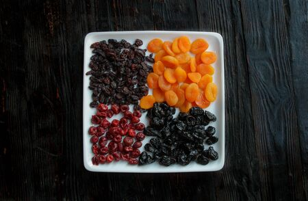 Dried fruits on a dark wooden background.Dried apricots, prunes, raisins, dried cherries on a square white plate.Copy space. Stockfoto
