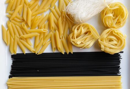 Close up of various types of dry pasta.Penne, spaghetti, noodles, black spaghetti, fettuccine, funchoz.