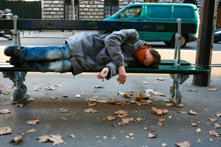 Drunk young man sleeping on a bench on the street. Autumn leaves on the pavement, traffic in the background.