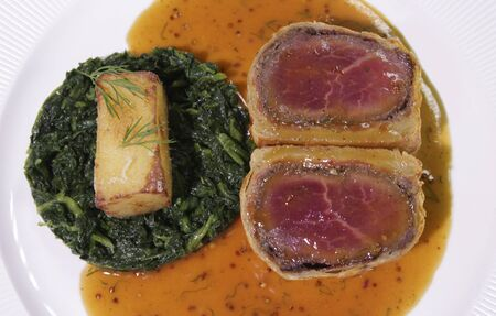 Carved Beef Wellington with Spinach and fried potatoes. Stockfoto