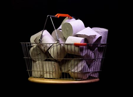 Shopping basket with rolls of toilet paper isolated on black Stockfoto