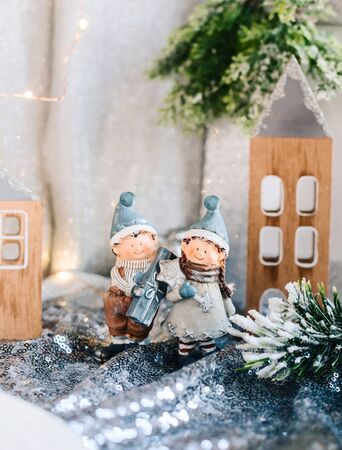 Porcelain figurines of children in a Christmas decor. Winter figurines of a boy and a girl with gifts on the background of houses and cones. Christmas Greeting card.
