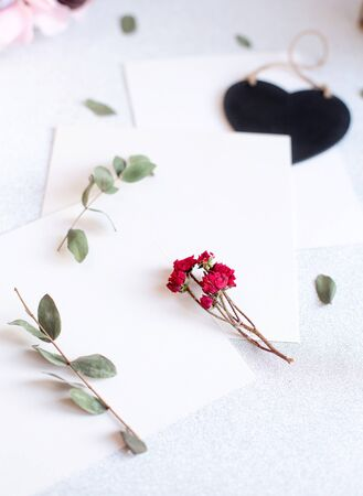Background with copy space blank on table with black heart, eucalyptus branch, roses flowers and leafs. White paper top view, flat lay, minimal style. Moke up card