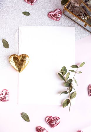 Background with copy space blank on table with glitter heart, eucalyptus branch, flowers and leafs. White paper top view, flat lay, minimal style. Moke up card Foto de archivo