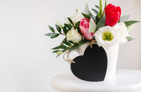 Black board heart copyspace. Spring bouquet in white vase on wooden white stand. Roses, tulips and lisianthus. Imagens