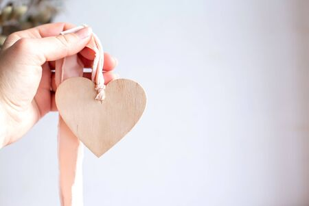 Light wooden heart on a silk pink ribbon. Hand holding a wooden heart pendant on a chiffon ribbon. Copy space.