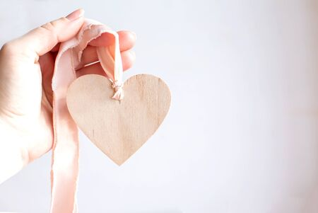 Light wooden heart on a silk pink ribbon. Hand holding a wooden heart pendant on a chiffon ribbon. Copy space. Imagens