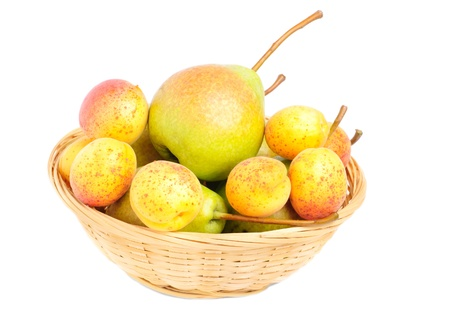 pears and apricots in fruit basket isolated on white background photo