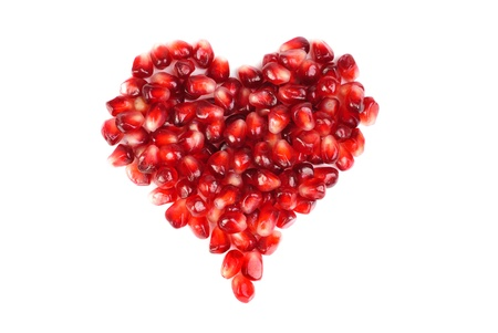 pomegranate seeds as heart shaped  isolated  on  white