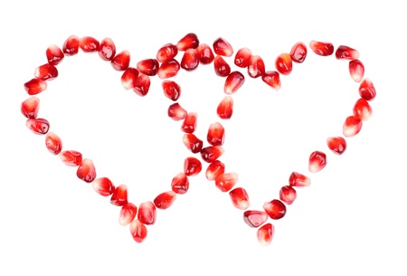 pomegranate seeds as heart shaped  isolated  on  white Stock Photo - 12200488