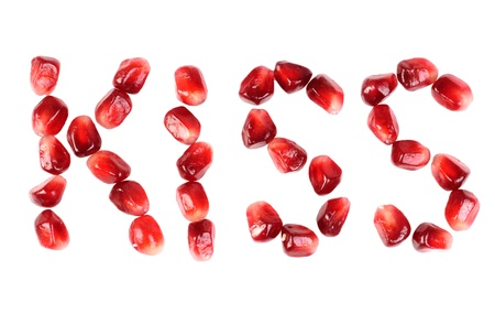 word of kiss  from the seeds of a pomegranate isolated on white  photo
