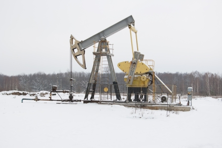 roughneck: oil pump works   on winter forest  background