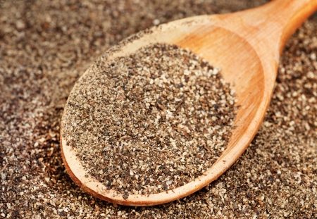 Ground black pepper (Piper nigrum) with wooden spoon