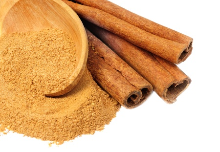 cinnimon: Cinnamon -  sticks and powder  and  wooden spoon  isolated  on  white