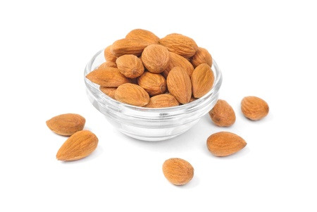 Dried almonds on glass bowl isolated on a white background  Stock Photo