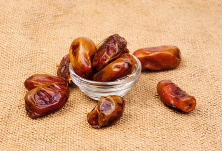 deglet: dried dates on glass bowl on canvas background