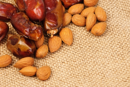 deglet: dried dates and almonds on canvas background