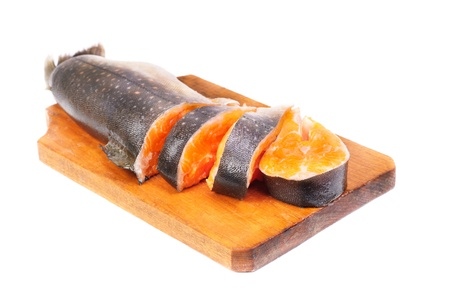 Salmon sliced on  cutting board, isolated on white background  photo