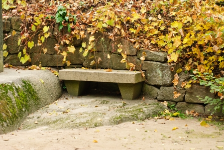 restful: Stone Park Bench with fallen and yellow leaves background