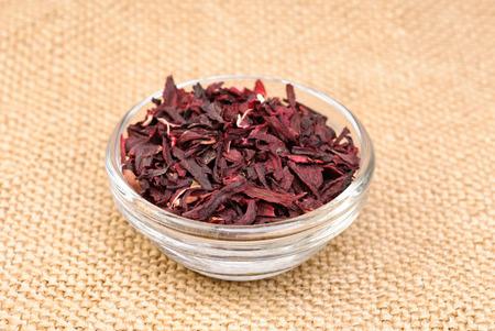 nontraditional: Hibiscus tea macro dry flower on sackcloth background Stock Photo
