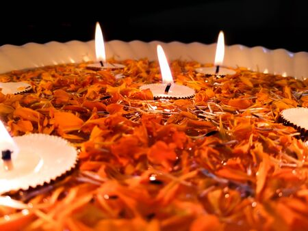 Happy Diwali, Tealight Candle Diya With Marigold Flower Floating in Water Inside Large Bowl 免版税图像