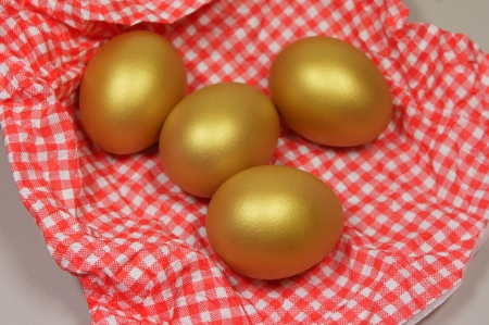 four golden eggs in a patterned napkin photo