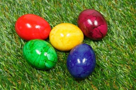 pasto sintetico: cinco huevos de colores se encuentran sobre un c�sped sint�tico