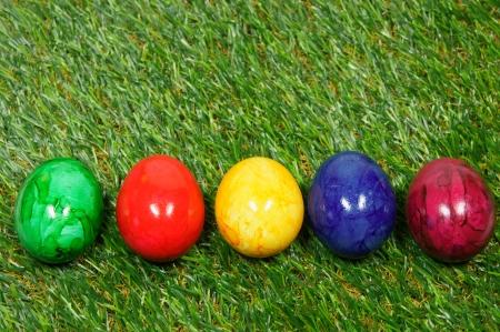 prato sintetico: cinque uova colorate si trovano su un erba sintetica Archivio Fotografico