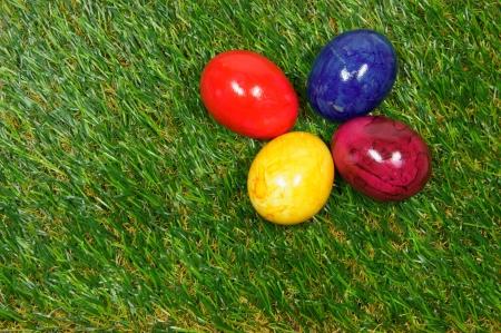 prato sintetico: quattro uova colorate si trovano su un erba sintetica
