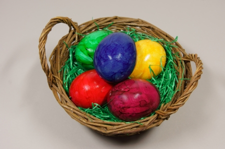 colorful eggs in a basket with green grass photo