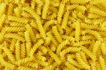 fussili: not cooked noodles fussili as background Stock Photo