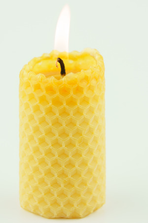 candle from honeycomb white background photo