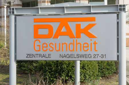 underwriter: Close up of a DAK healthcare sign and logo in Hamburg showing the address, providing public health insurance