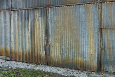 large doors: Old rusty galvanised corrugated iron building with large closed double doors viewed at an oblique angle Stock Photo